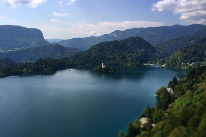 Bird's-eye view of a deep blue lake and green, forested mountains