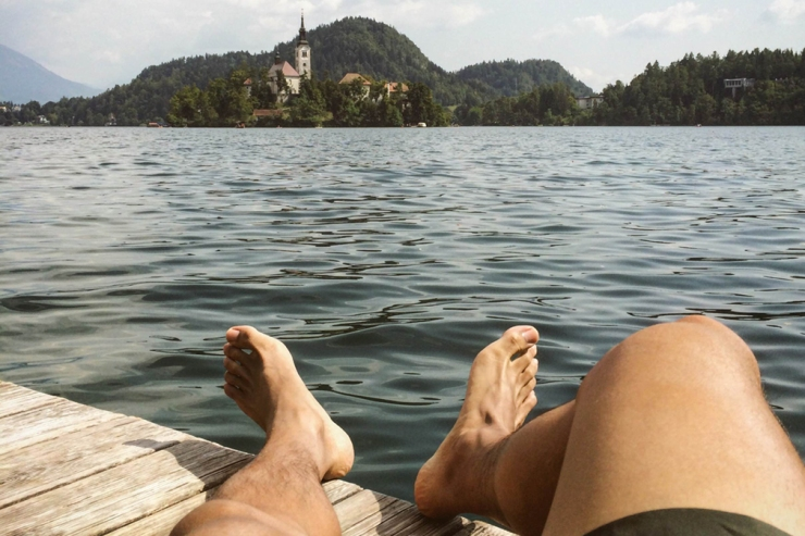 A pair of feet outstretched on a lakeside dock with a chapel in the distance