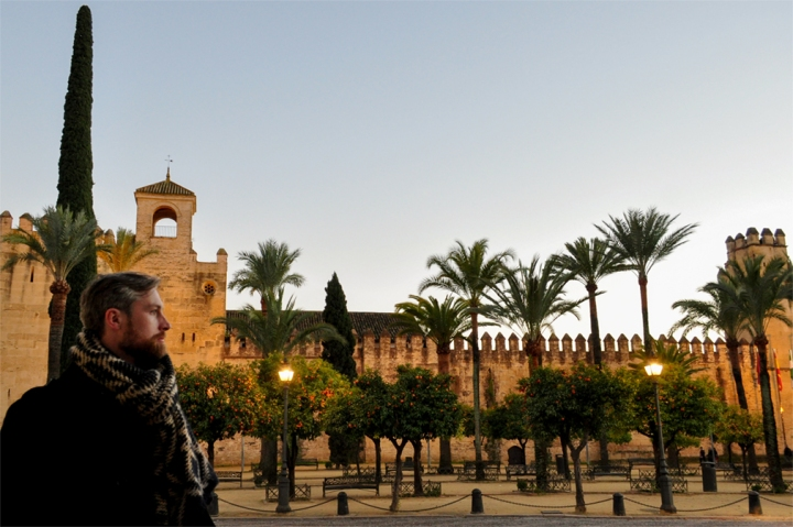 Man in front of a medieval Moorish palace with palm and orange trees