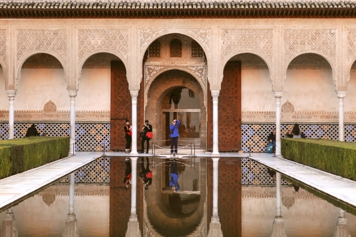 Interior of the Alhambra with intricately carved stucco columns and reflecting pool