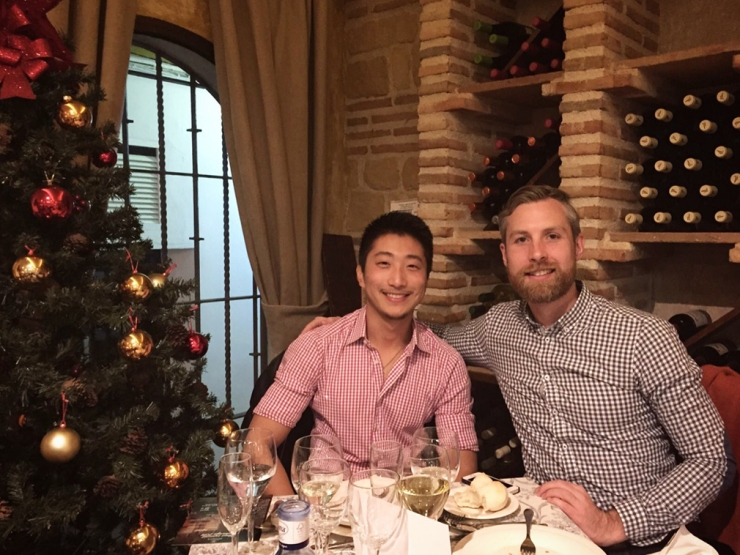 A couple in gingham shirts posing for Christmas dinner