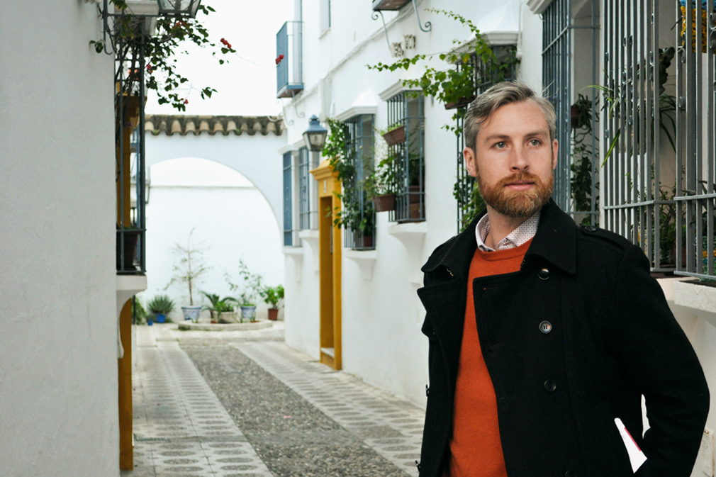 Man in a narrow alleyway with white buildings and hanging plants