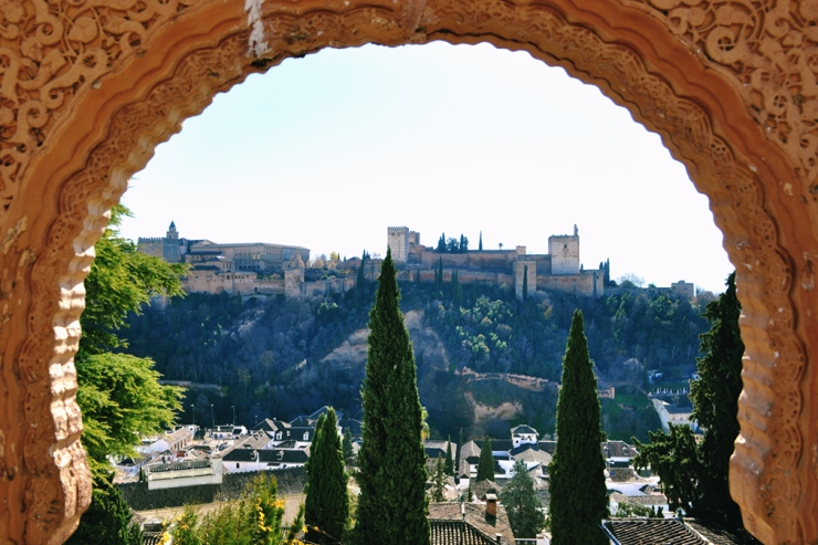 Panorama of the fortress of the Alhambra as seen through an intricate stucco archway