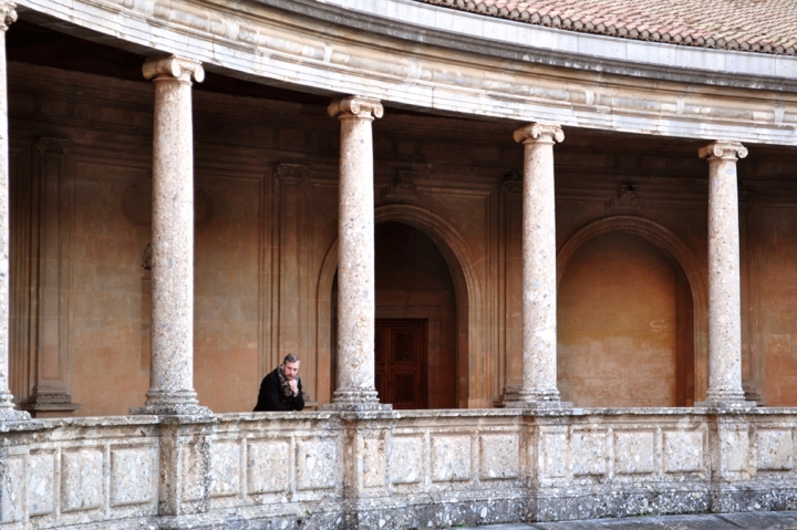 Man on the balcony of a large Florentine-style patio with Ionic columns