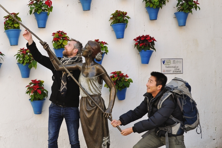 Two men posing with a bronze statue in a public patio