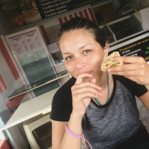 A young woman enjoys a faratha, a Mauritian stuffed flatbread dish of Indian origins