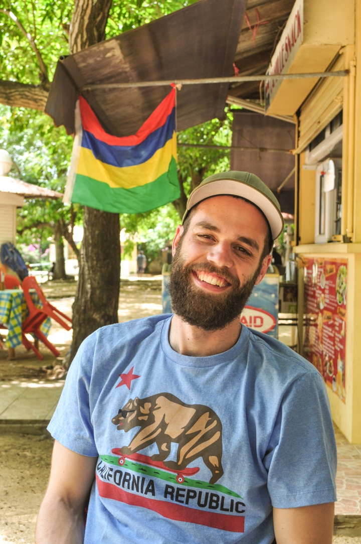 A young bearded man smiles in front of a Mauritian flag