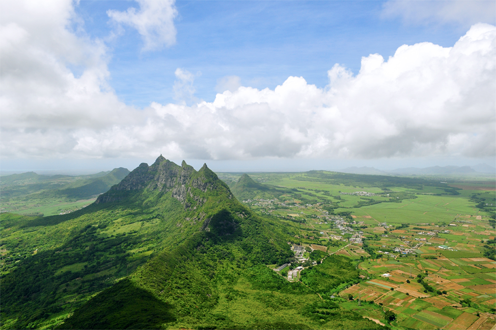 Panoramic view of a mountain range jutting out from the green earth