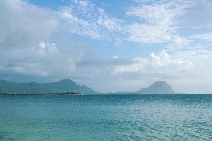 A calm tropical ocean with mountains in the distance