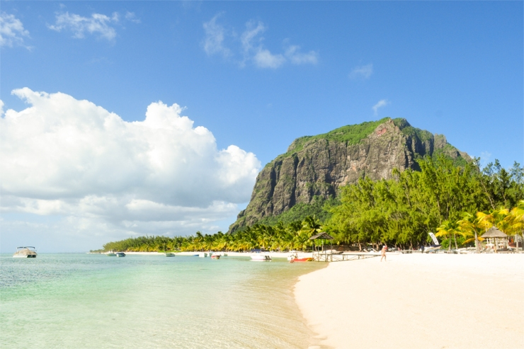 A tropical, sandy beach with transparent waters and a mountain backdrop