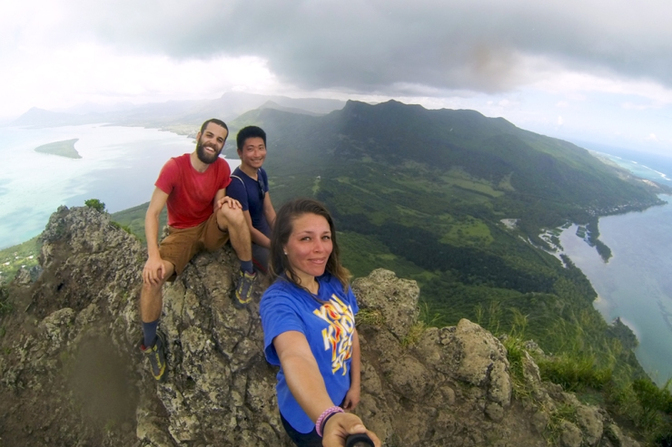 A trio of young hikers atop a mountain summit