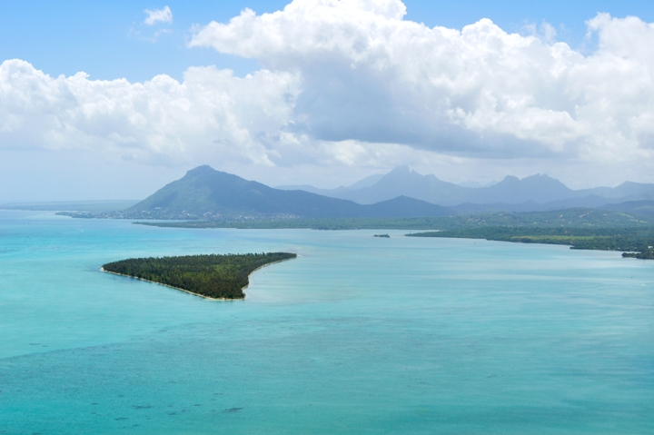 Panoramic view of turquoise waters, a forested island, and mountains