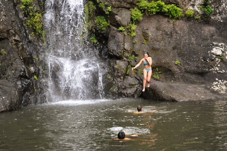 Young woman jumping into the pool of a waterfall