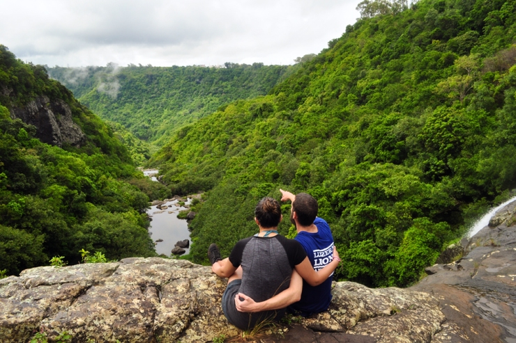 A young couple admire the lush landscape of a gorge from atop a waterfall