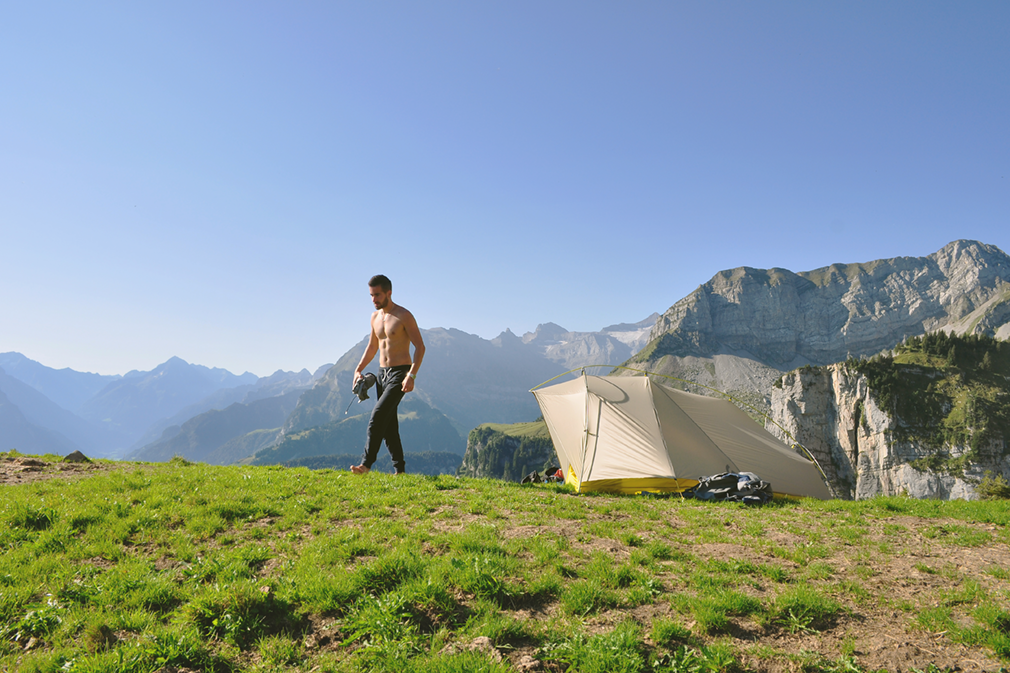 A man emerging from a tent with mountains in the background