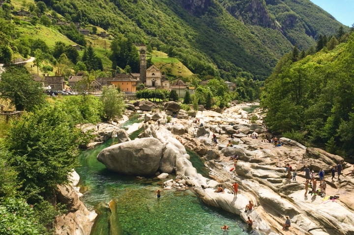 A river flows past rounded bolders of granite in a valley