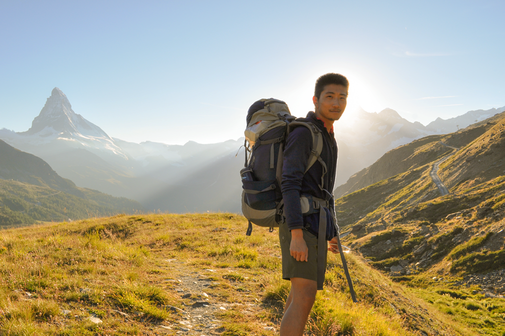 Young man with backpack hiking in sunset