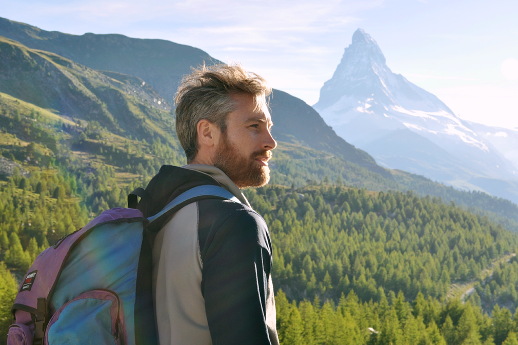 A man with a backpack looks at a forested scenery featuring the Matterhorn