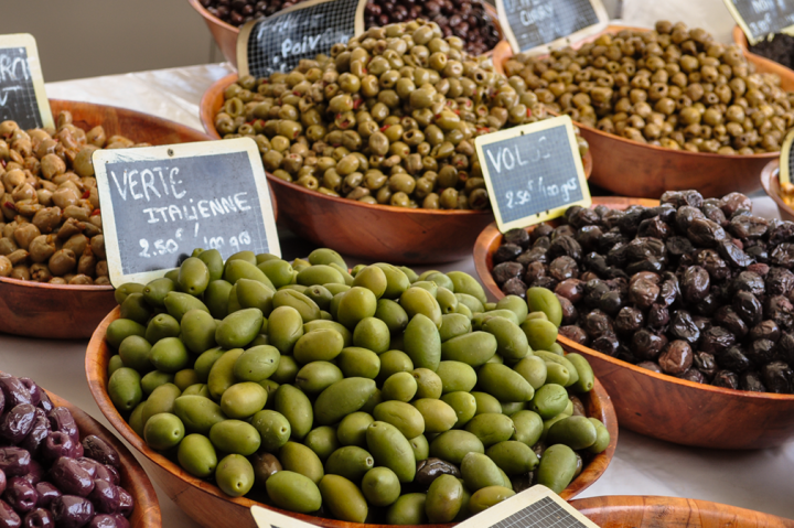 Bowls of colorful olives on display in open-air market