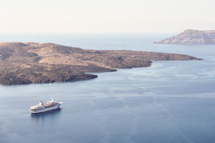 Cruise ship sailing past arid island