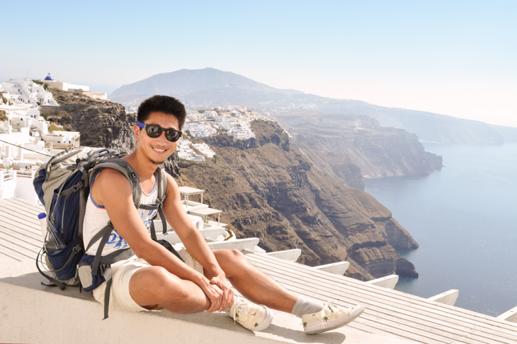 Smiling man in sunglasses and shorts on a white balcony in front of high cliffs