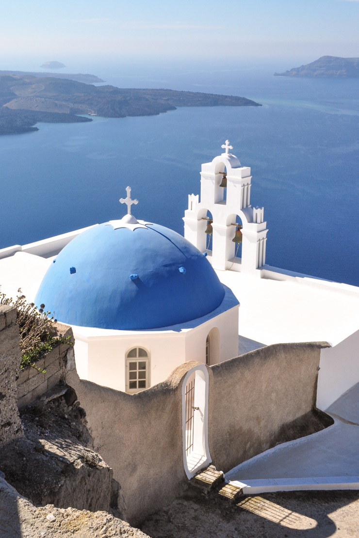 Blue-domed church with three bells overlooking the sea
