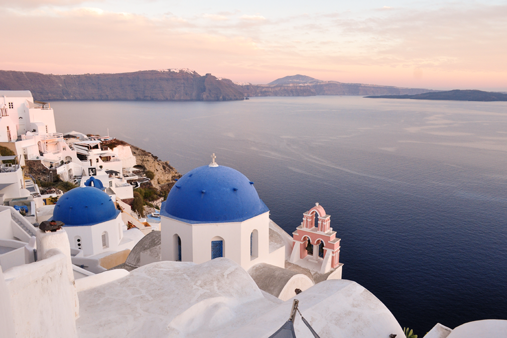 Blue-domed churches and white buildings on clifftop in sunset