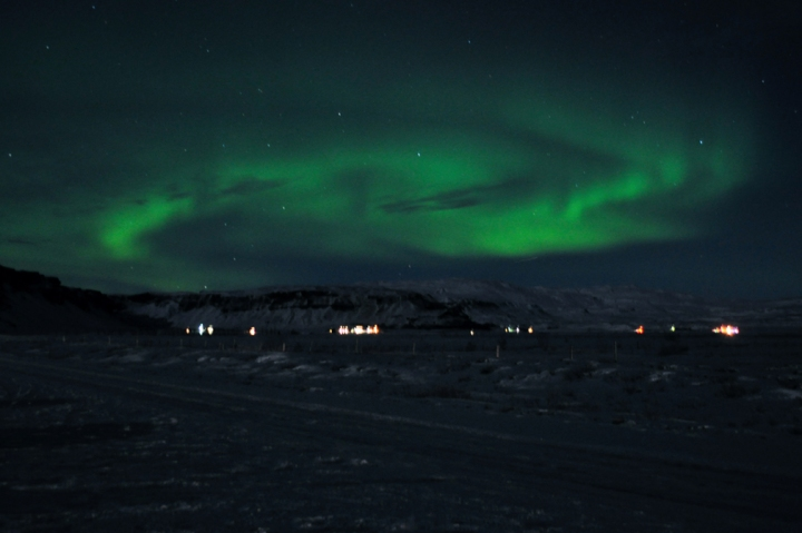 Northern lights dancing above small villages