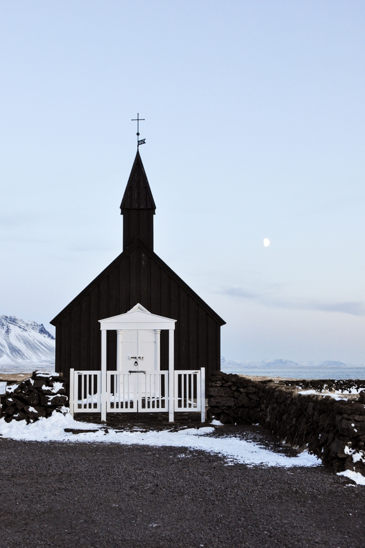 A black church with a white door by the ocean
