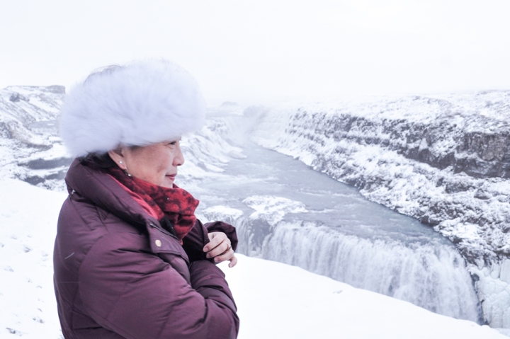Woman in winter clothing standing by a partially frozen waterfall