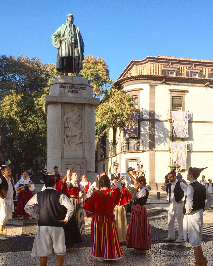 Dancers in traditional folk costumes gather beneath a statue