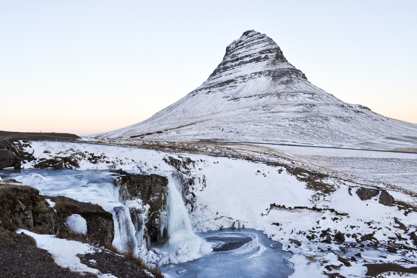 Triangle-shaped mountain behind a frozen waterfall