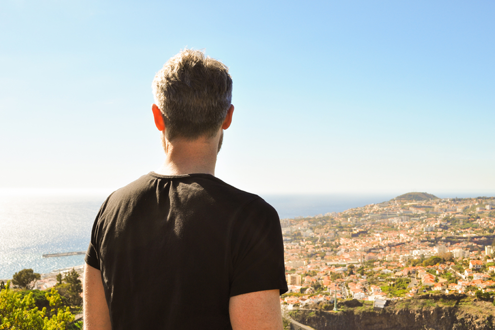 Man in black shirt looking over a city and the ocean