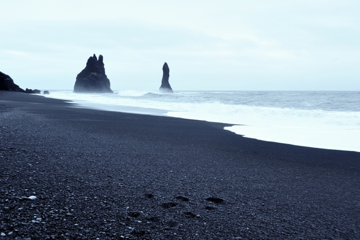 A beautiful volcanic black sand beach with jagged basalt sea stacks in the distance