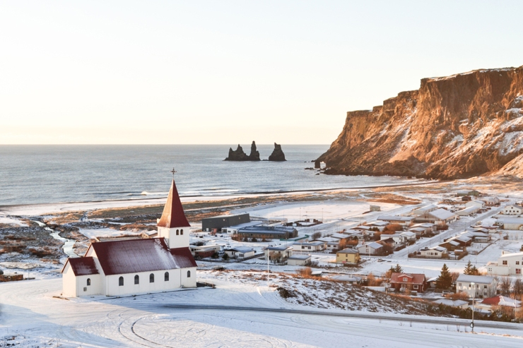 A church overlooks a wintry coastline with cliffs in the distance