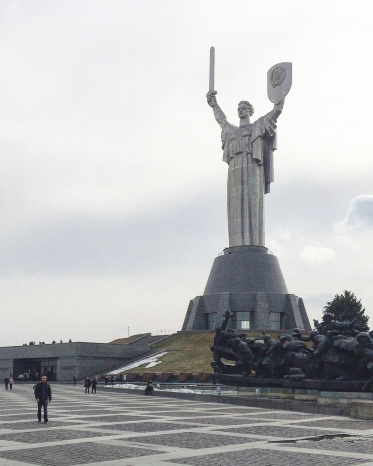 Large monument of woman draped in frock holding sword and shield