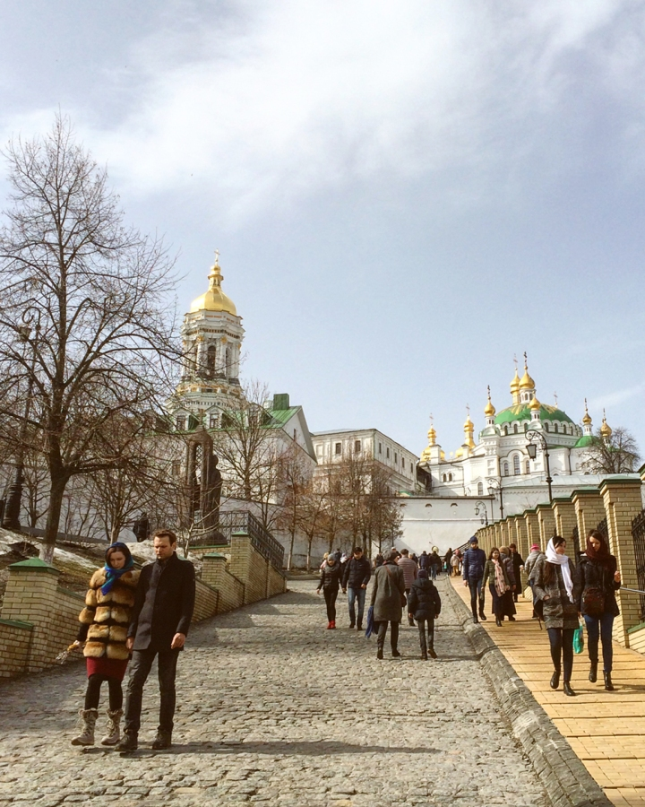 People promenading down the sloping hill of a monastery with golden spires and green domes
