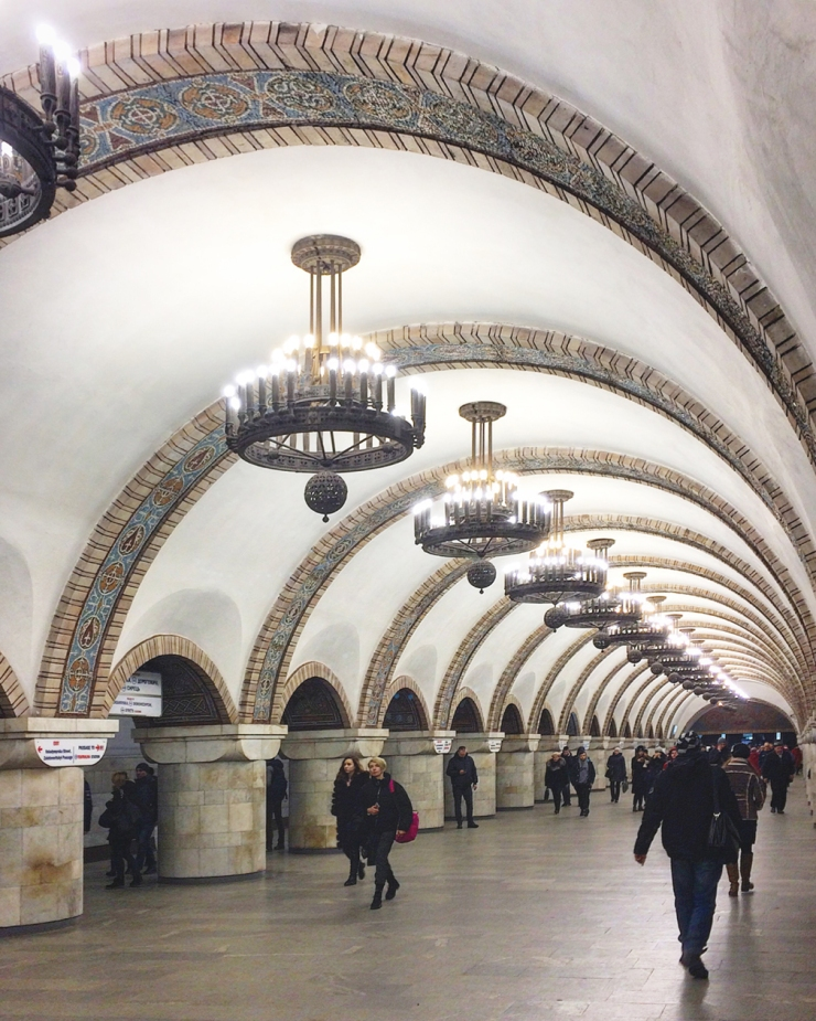 An underground passageway featuring large chandeliers and mosaics