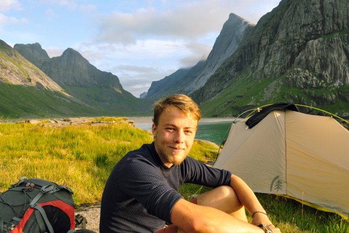 Blond man sitting in front of tent by the beach