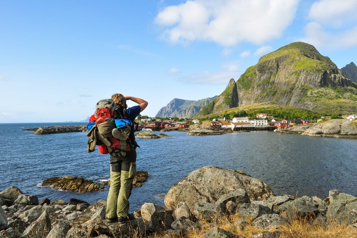 A person in a backpack takes a photo of a fishing village