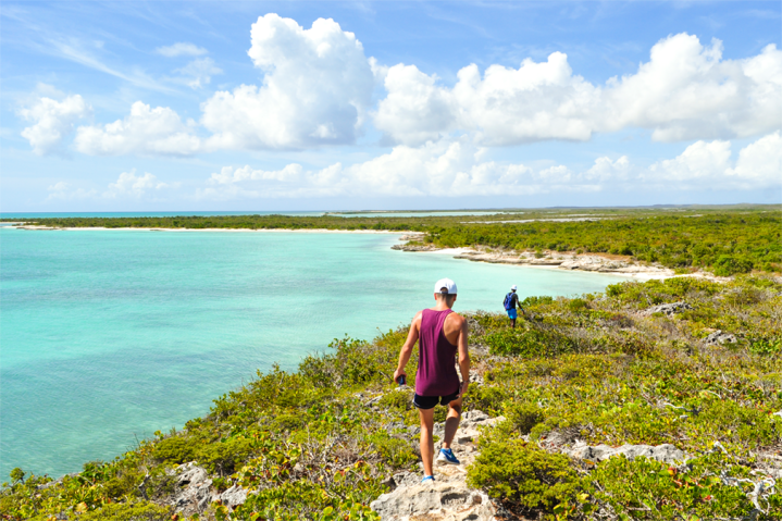 Two men hiking down a trail overlooking the ocean