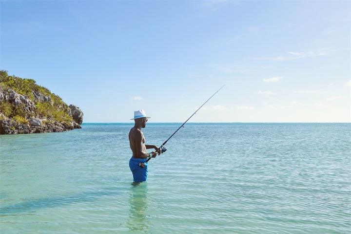 Man in hat and blue swim shorts fishing in ocean