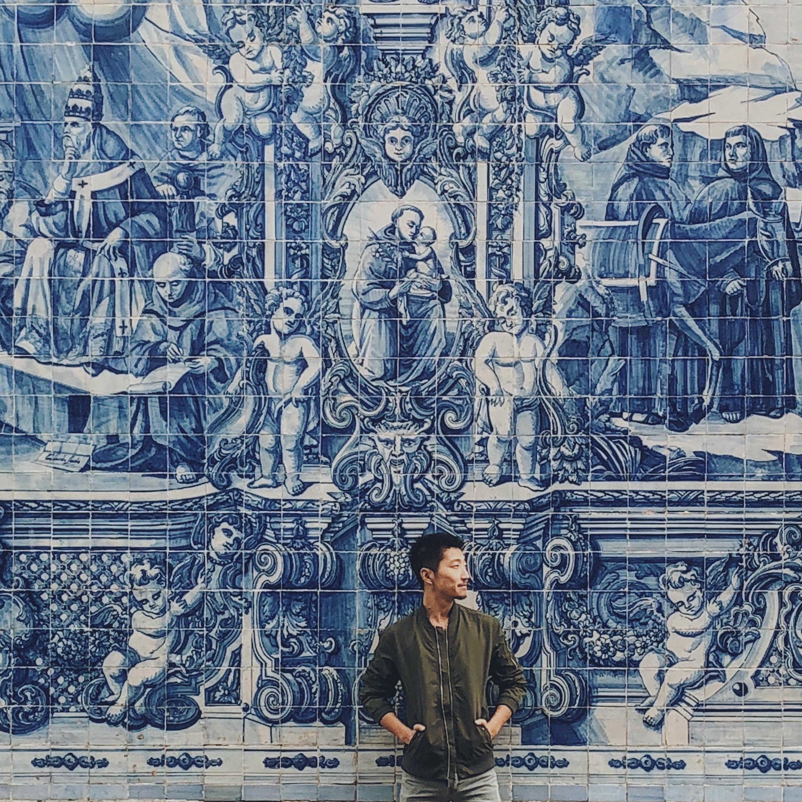 Man standing in front of blue tin-glazed ceramic tiled façade