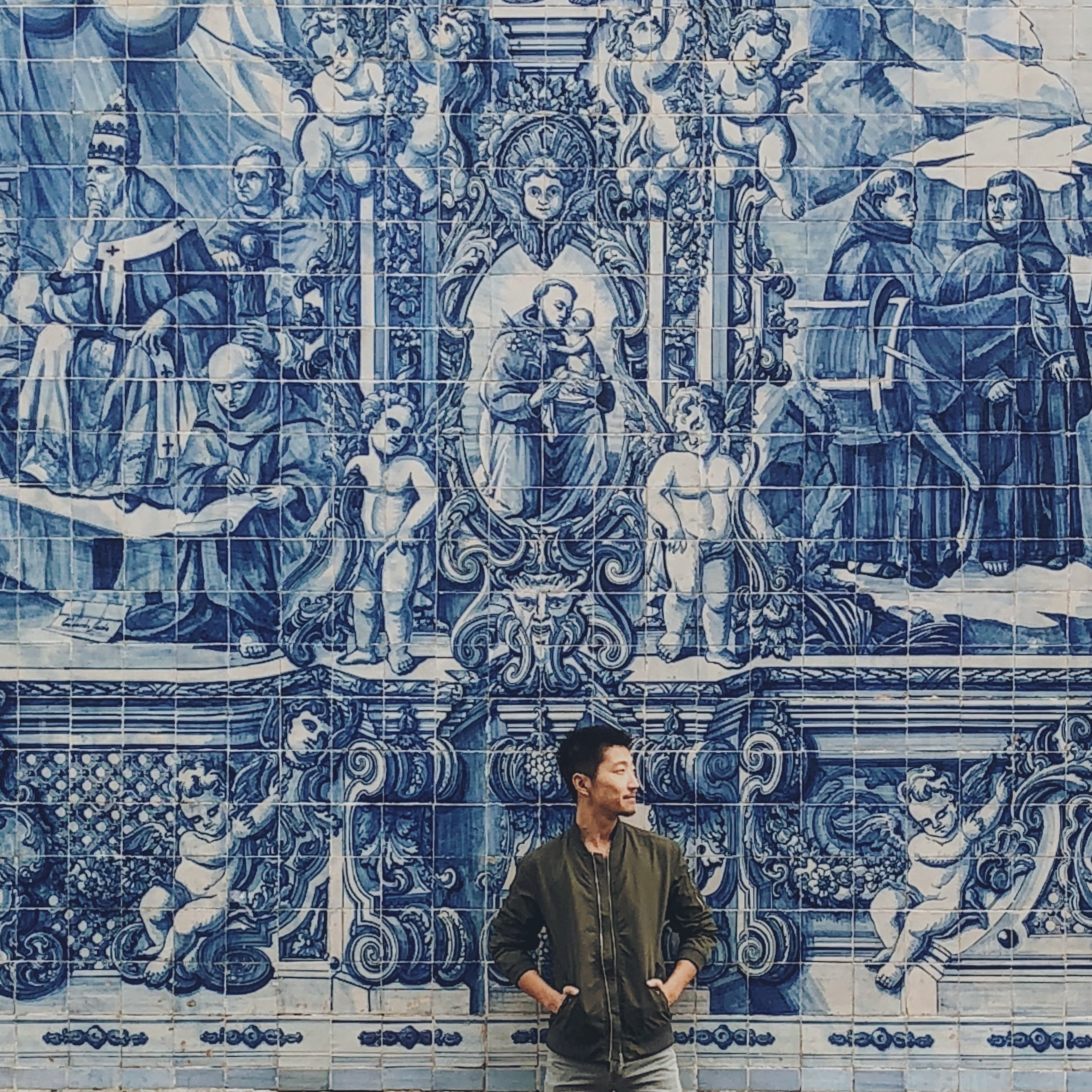 Man standing in front of blue tin-glazed ceramic tiled façade
