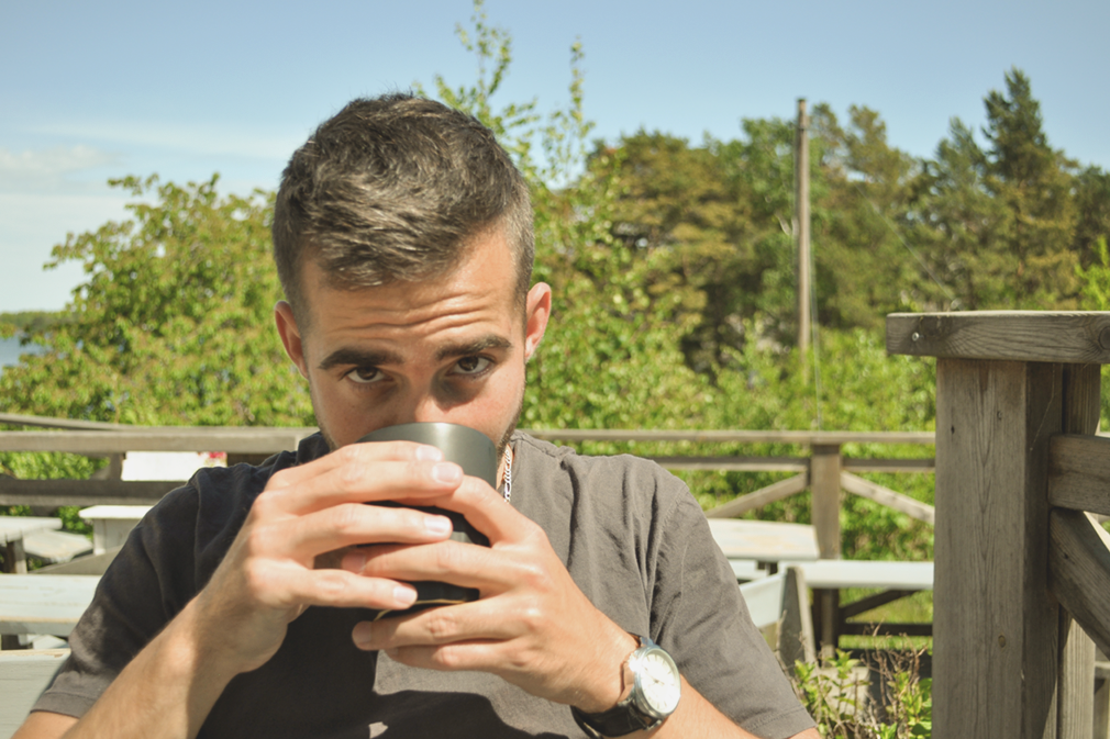 Man drinking coffee on a wooden terrace