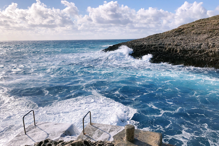 Waves crash onto the rocks at Malta's Blue Grotto