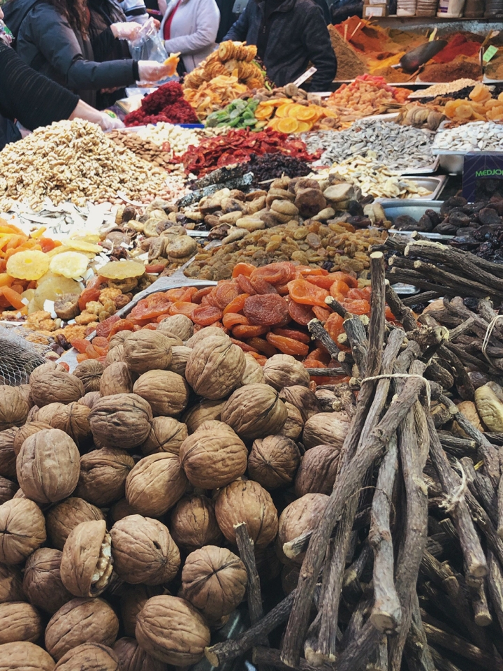 A marketplace scene with walnuts, apricots, and dried fruits on sale