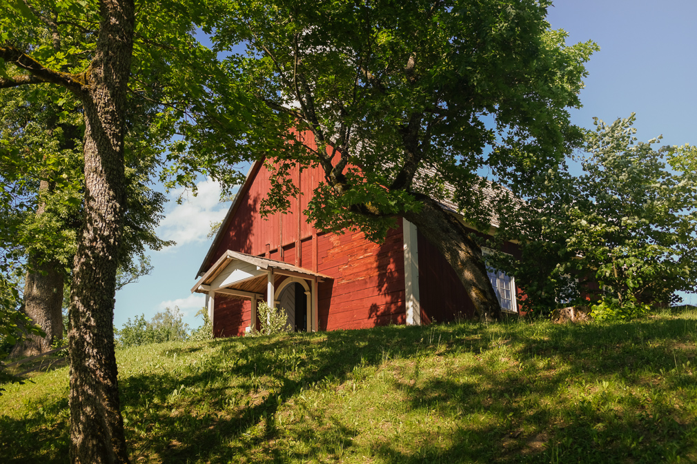 A red wooden church in the summer shade