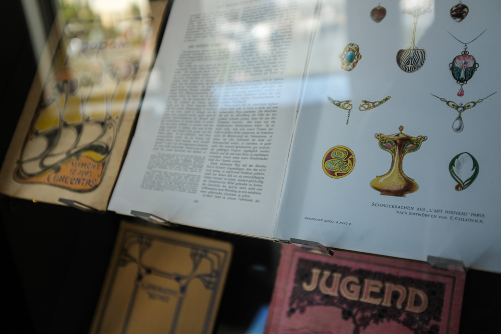 A close-up of Art Nouveau books through a glass display