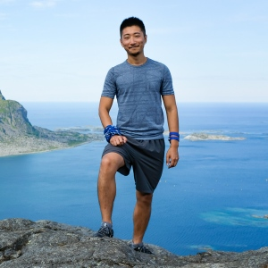 Smiling man posing in front of ocean and mountain island